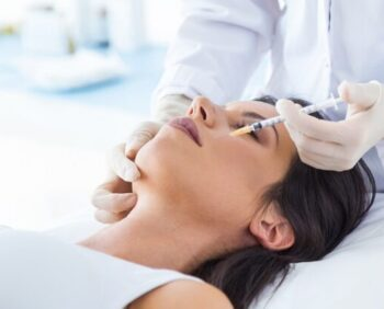 Beautiful young woman getting botox cosmetic injection in her fa